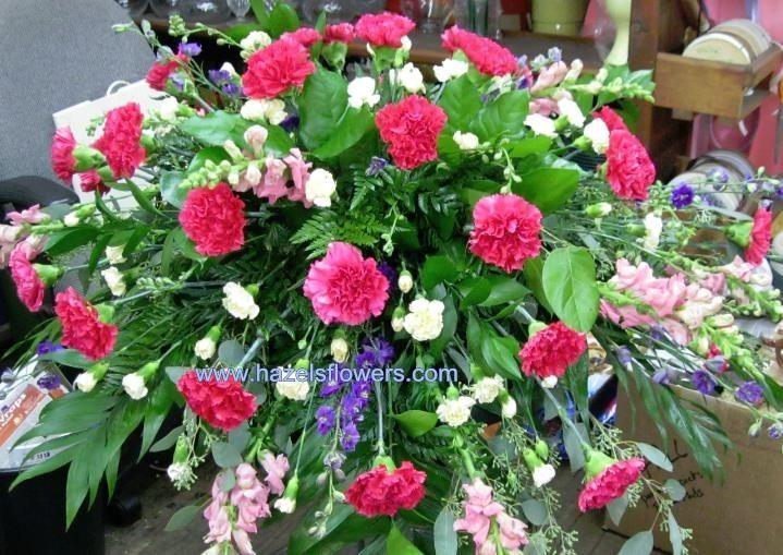 Casket spray tribute in hot pink carnations, buttercream pixies, purple larkspur & assorted greens