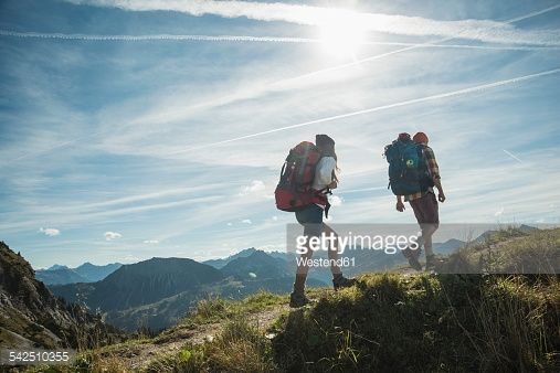 Stock Photo : Austria, Tyrol, Tannheimer Tal, young couple hiking on mountain trail