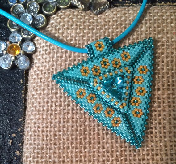 This peyote stitched triangle shaped pendant is made up of shades of turquoise and golden yellow Delica seed beads with a Swarovski rivoli crystal