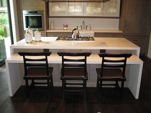 White Concrete Two Tier Waterfall Kitchen Island With Gray Wash Cabinets.