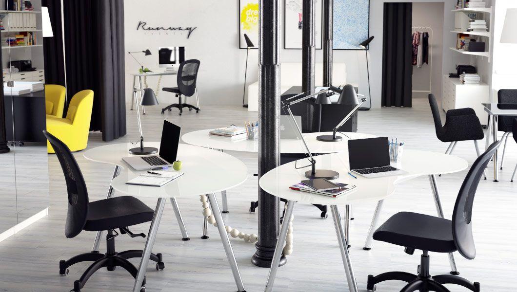 Agência de RP decorada com secretárias, poltronas giratórias e sofá de pele