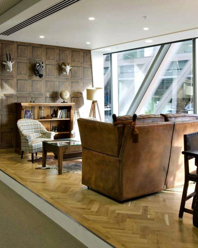 This meeting space at Dealogic has been inspired by a traditional hunting lodge with wall-mounted animal heads, worn leather sofas, tartan check arm chair and wood book shelves and coffee table.  The traditional decor contrasts with the ultra-modern floor to ceiling windows which flood the space with natural light.