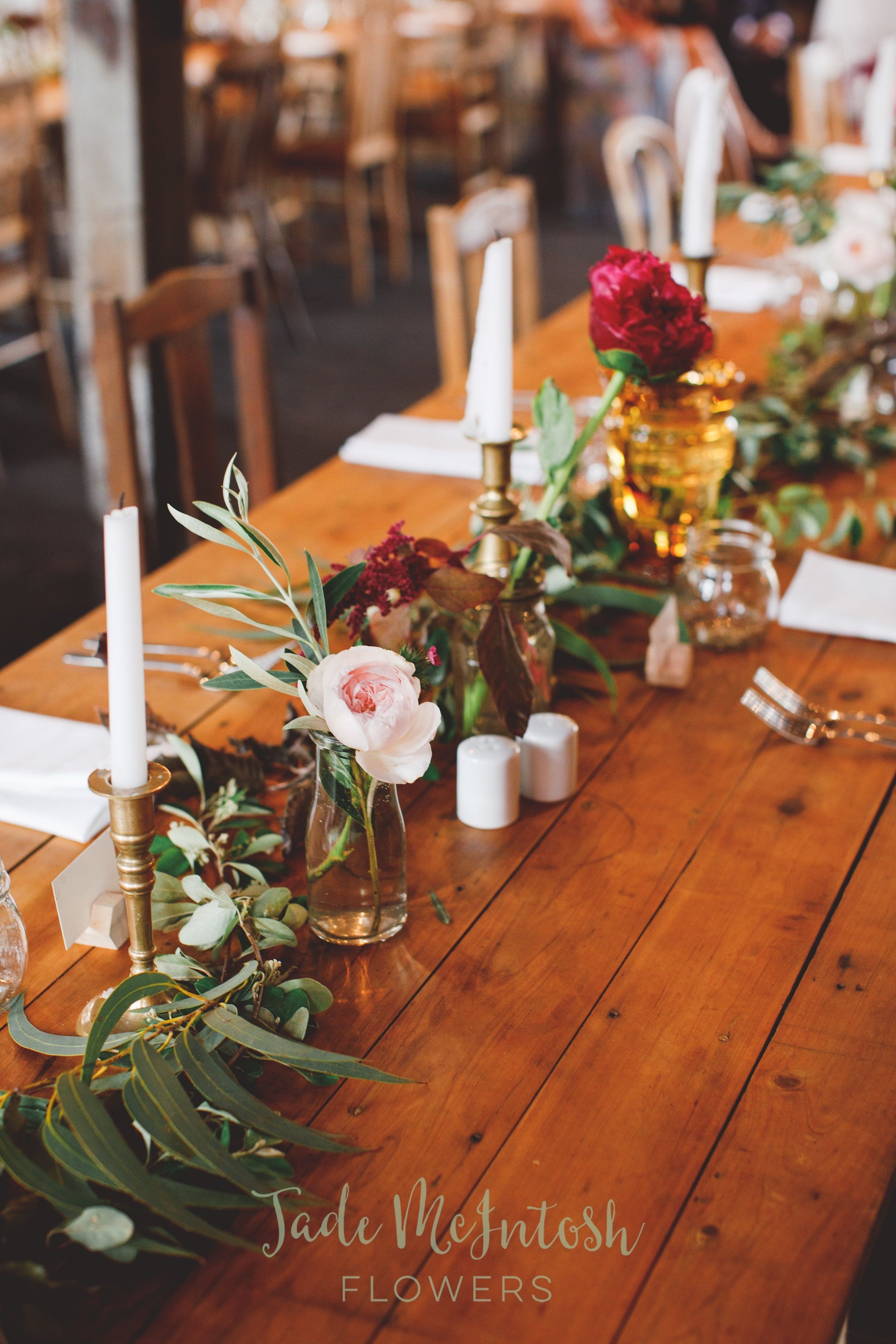 The Combination Of Single Stems In Glass Jars Gum Foliage And Brass Candlesticks Is A Winner Www Wedding Table Vases Head Table Wedding Round Wedding Tables