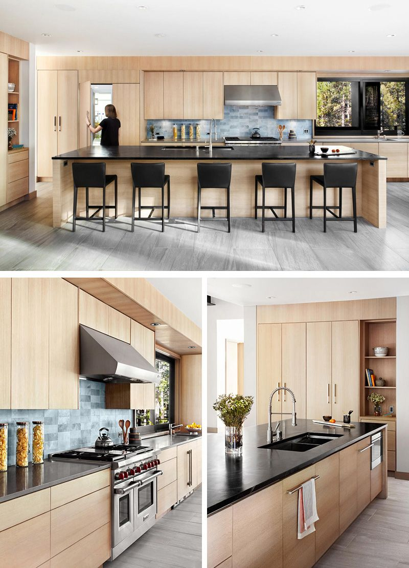 This kitchen features light wood cabinetry, dark countertops with a ...