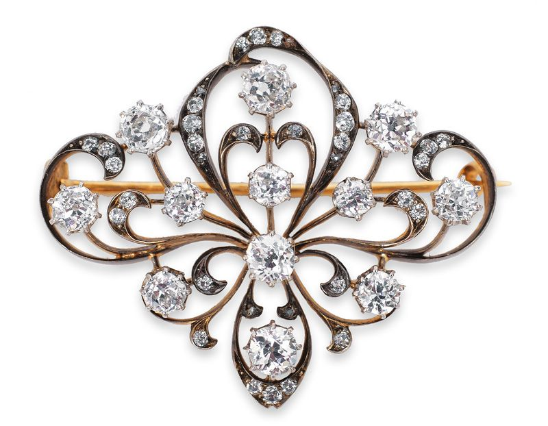 A diamond brooch  C. 1900. 14 kt. yellow gold/silver, with 12 old cut diamonds and 35 diamonds, total c. 3 ct. SI-P/H-J. 34 x 41 mm.