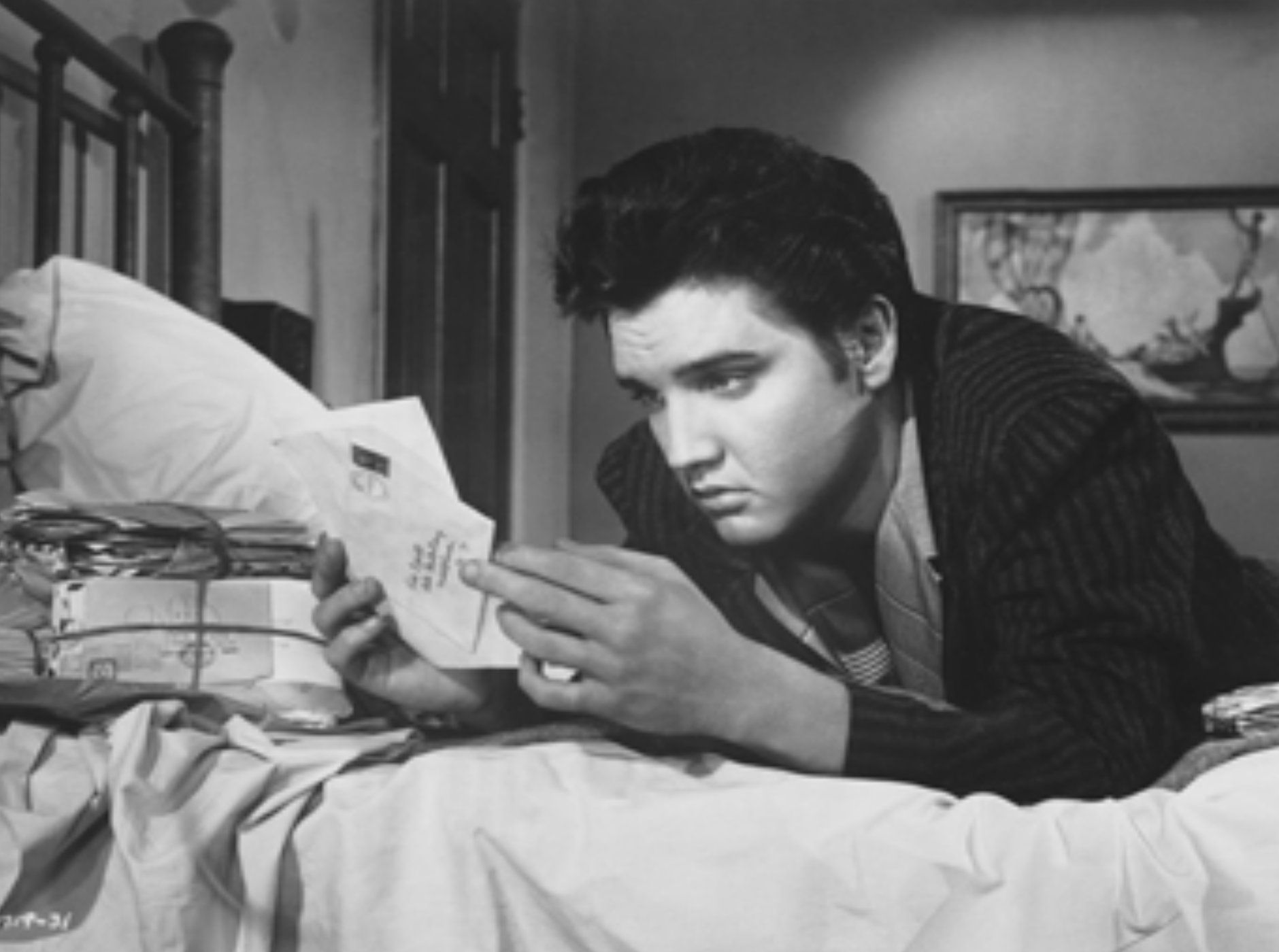 Elvis reading fan mail on his bed