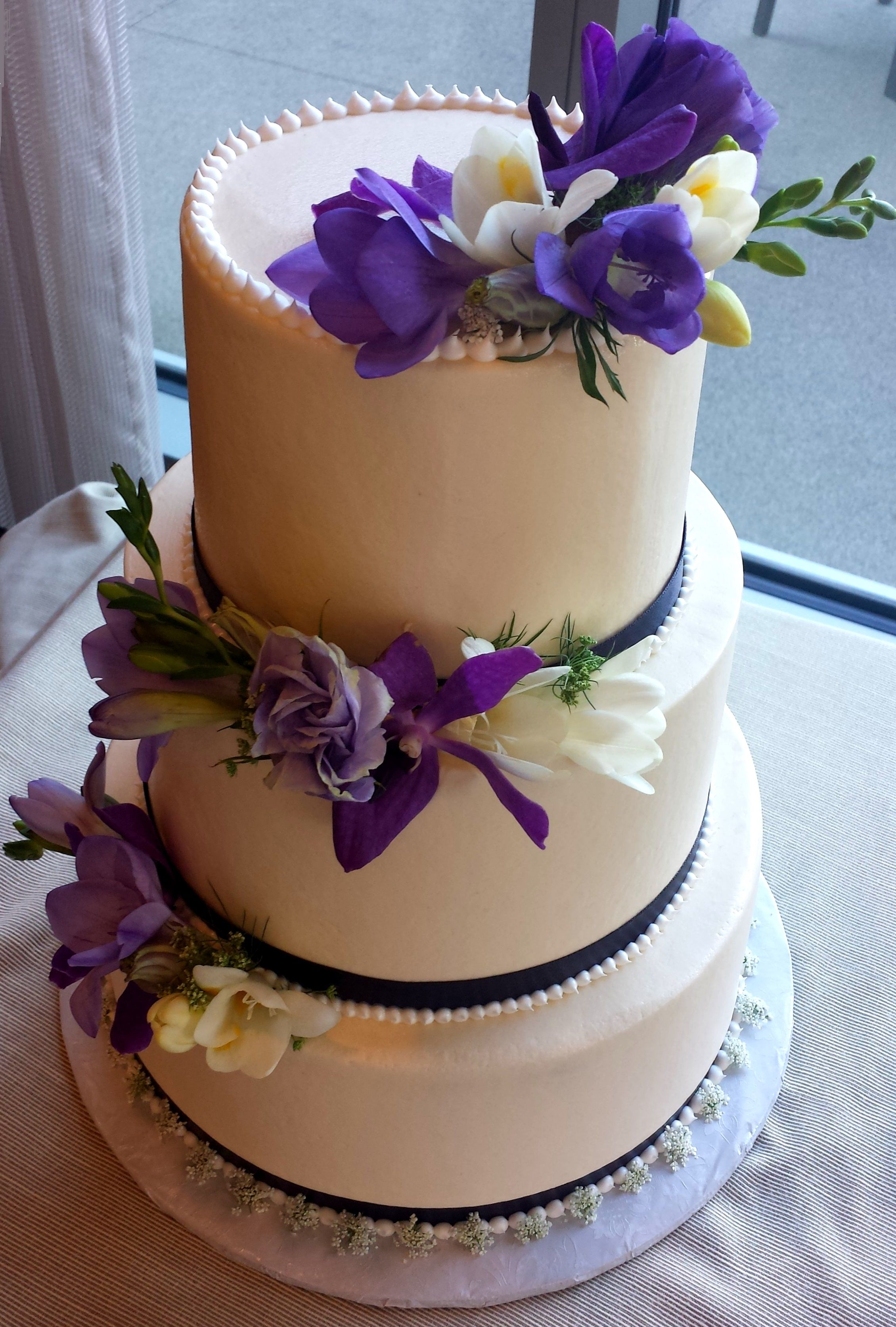 Butter cream wedding cake with with flower accents. Lake