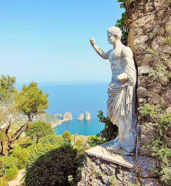 View of the famous Faraglioni rocks from the top of Mt Solaro, and next to a Roman statue. Capri Naples Campania