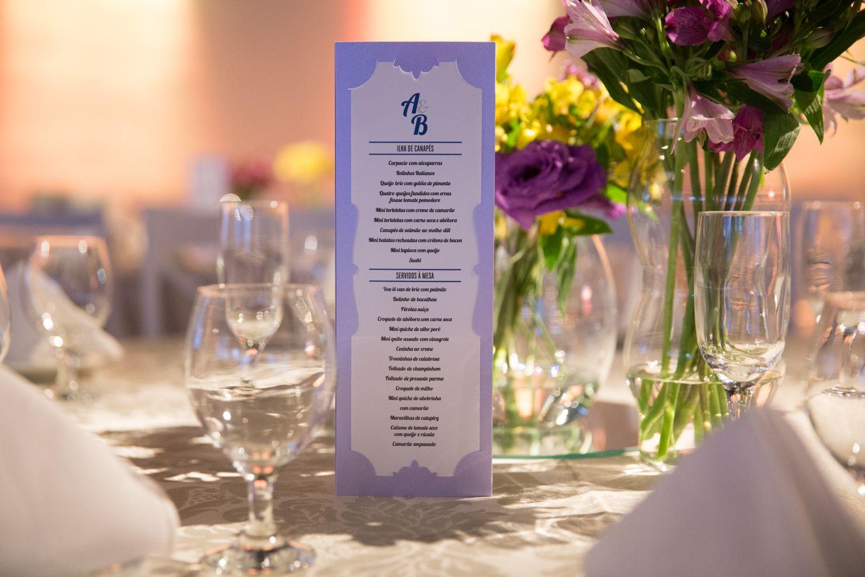 Menus cuidadosamente pensado pelos noivos 💜 flores amarelas e roxas e muitos vidros nas mesas dos convidados. #limoeirodecor #wedding