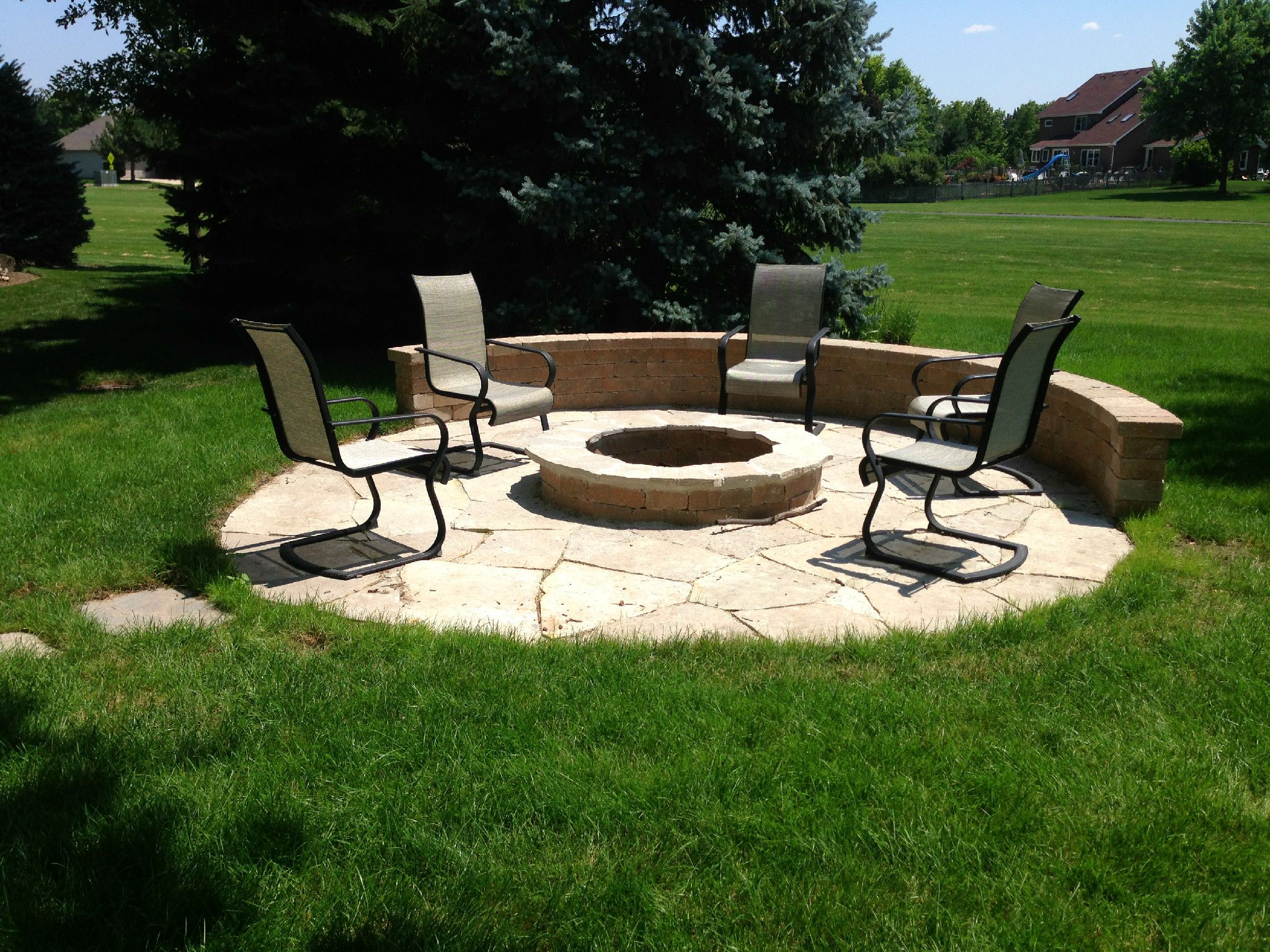 circular patio with built in fire pit and seat wall by naperville