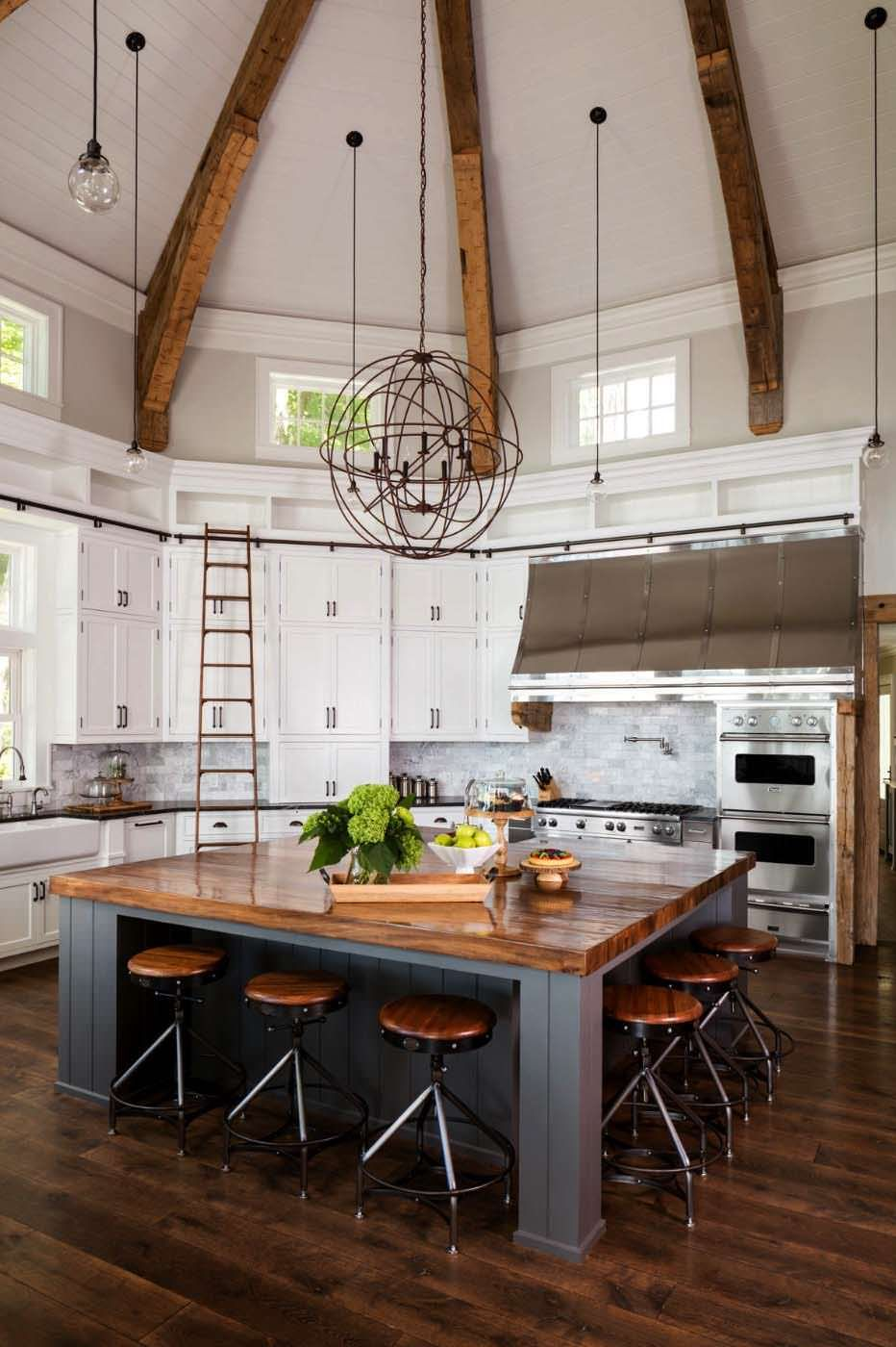 Photo of Open kitchen with a vaulted ceiling and large central wooden…