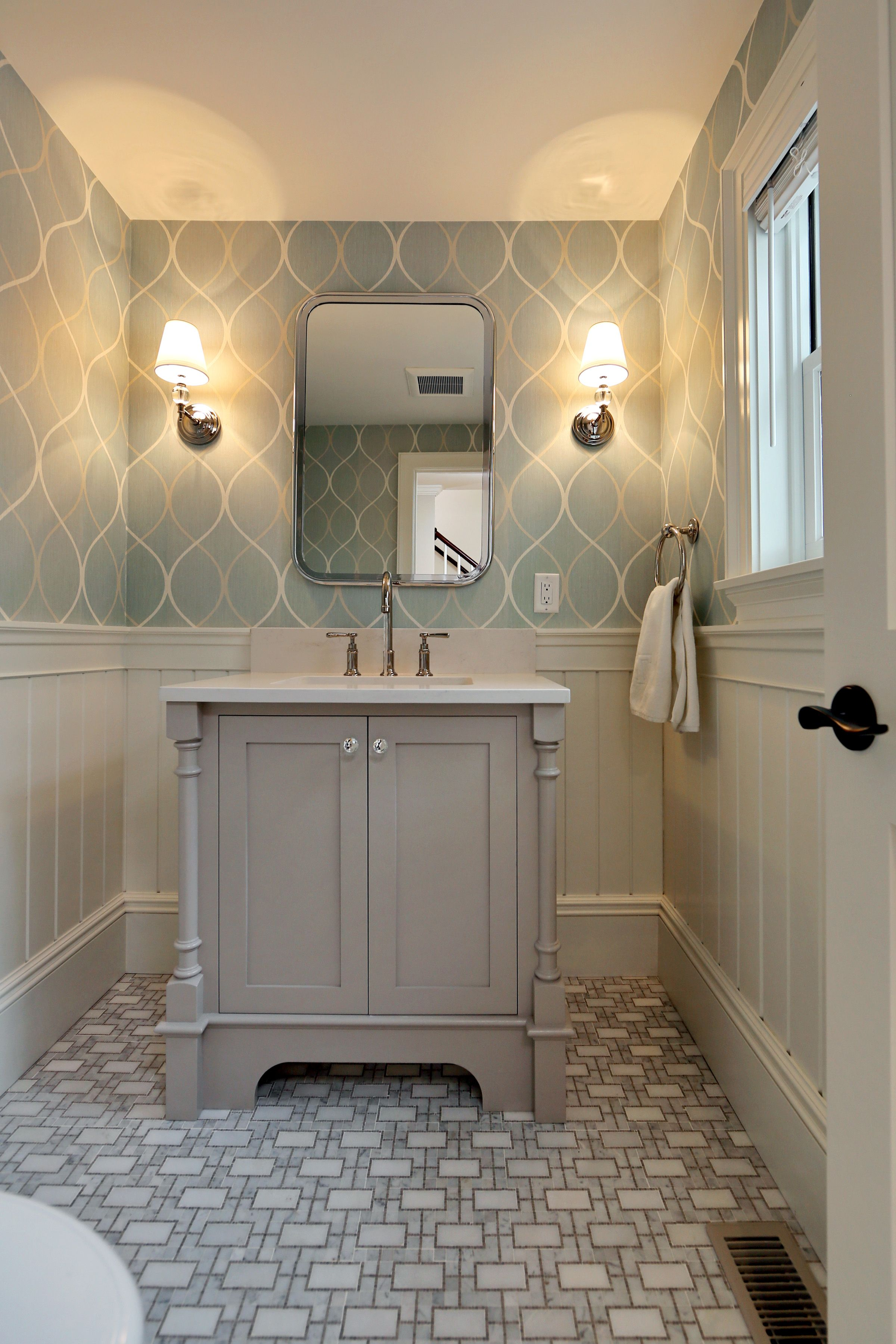 grey vanity with wallpaper and patterned tile www encoreco com