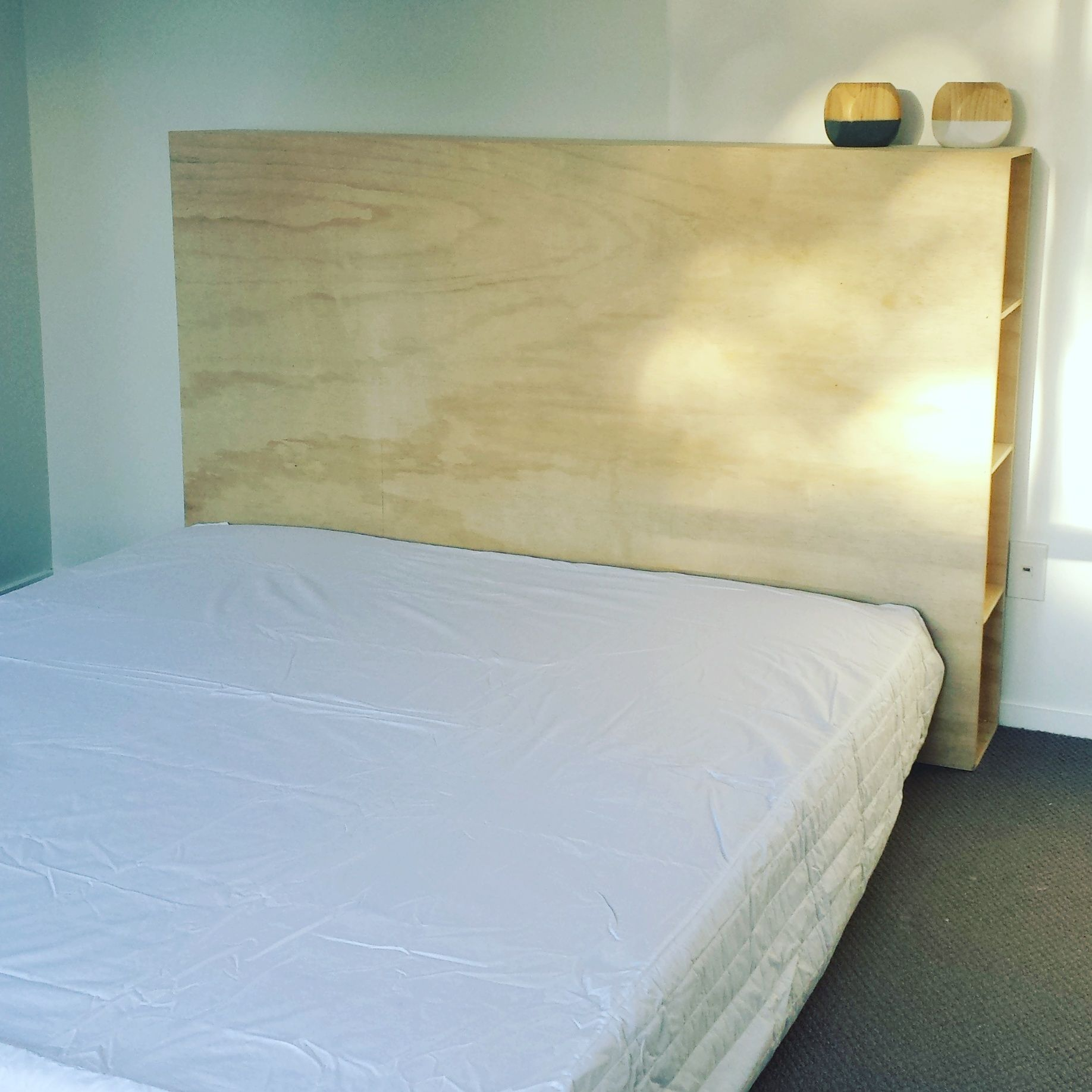 Our plywood headboard with shelves down the side so we no longer