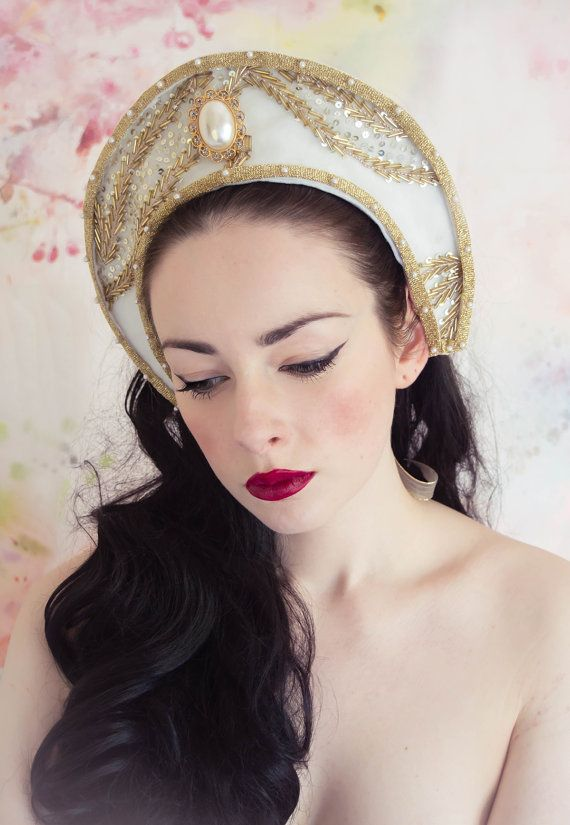 This pretty piece is inspired by Tudor headdress, and is made from a base of soft felt fabric and chiffon. It is adorned with a central gold and