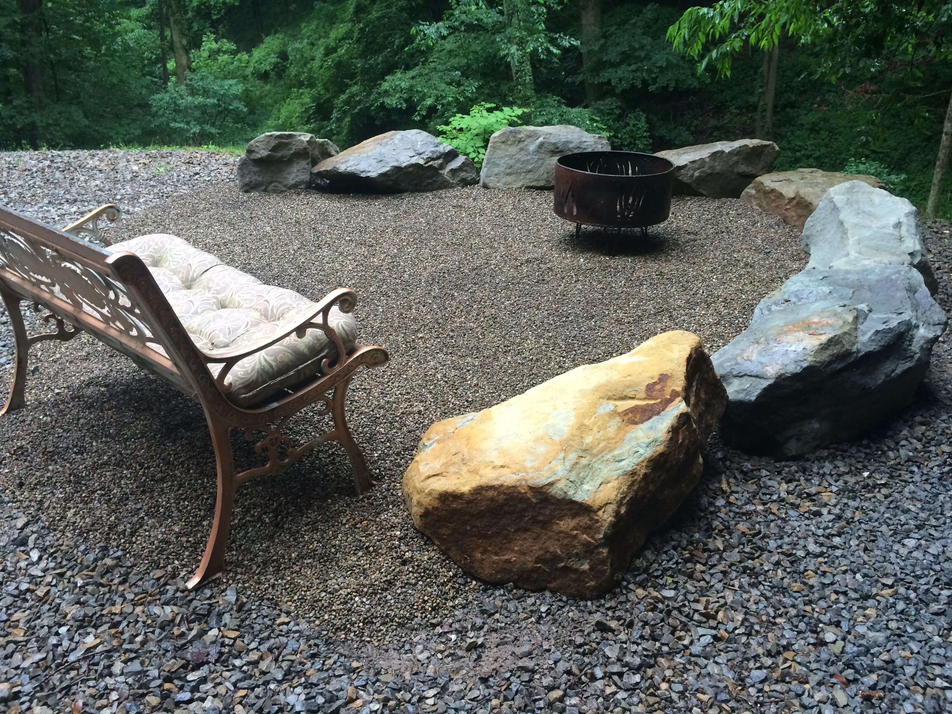 fire pit area we created with boulders and pea gravel backyard