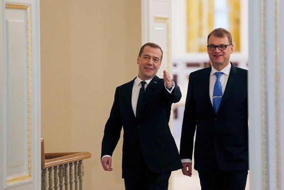 Venäjän pääministeri Dmitri Medvedev ja Suomen pääministeri Juha Sipilä tulevat suurista ovista. Miehillä on yllään mustat puvut, Sipilällä on sininen kravatti ja Medvedevillä tumma. Molemmat hymyilevät. Medvedev viittoo huoneen sisälle päin.
