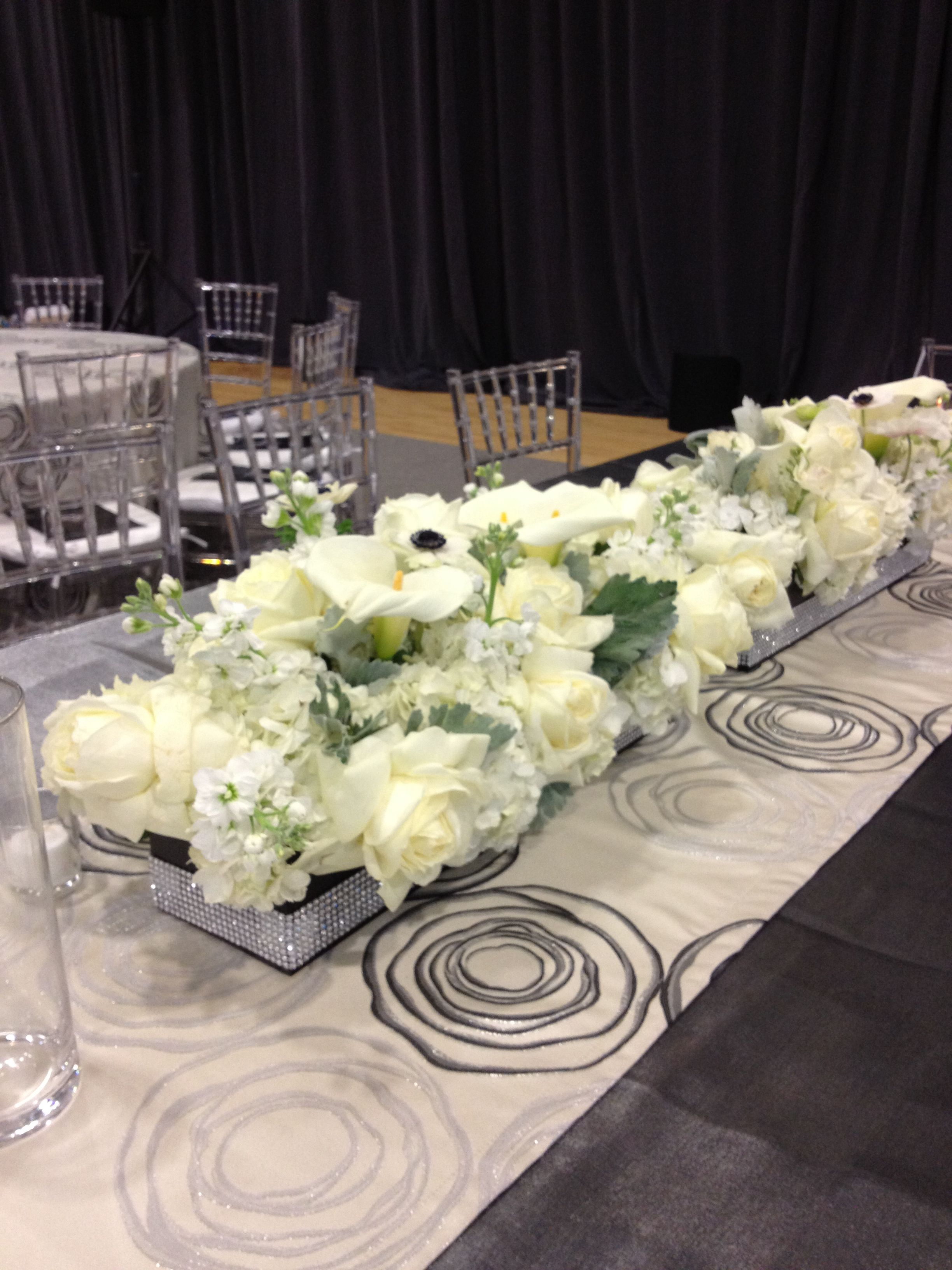 All white floral centerpiece in a rectangle box with