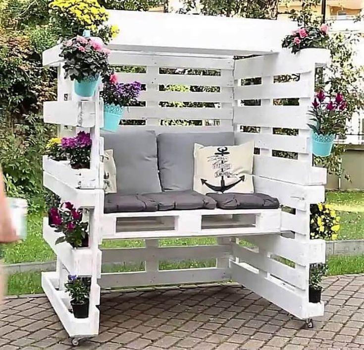 Photo of Geschlossener Sitzbereich aus Holzpalette mit bequemen Kissen