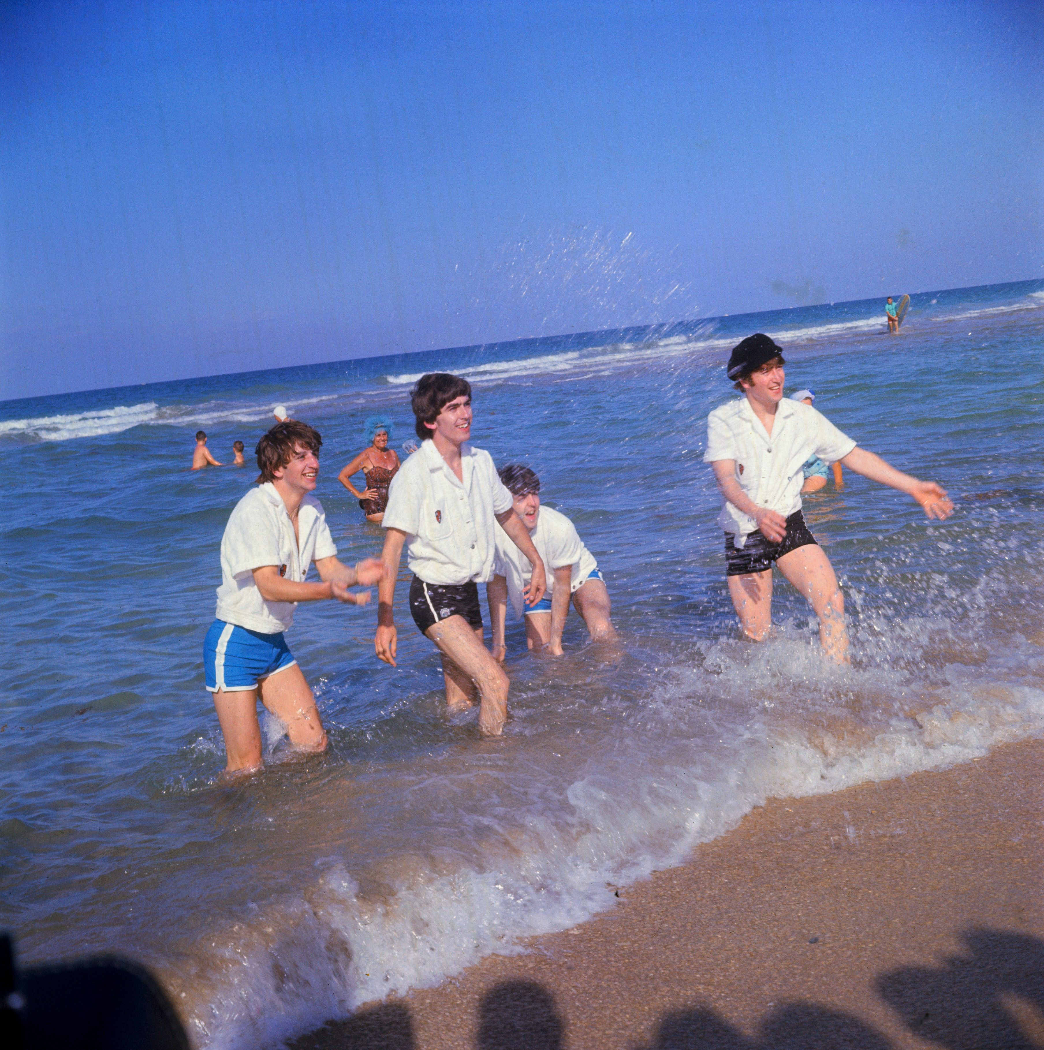 15 Feb 1964, Miami Beach, Florida, USA --- Ringo Starr, George Harrison, Paul McCartney, and John Lennon (L-R) splash onlookers while wading along the surf in Miami Beach, Florida. The Fab Four are in town to perform for a second time on The Ed Sullivan Show. --- Image ©Bettmann/CORBIS