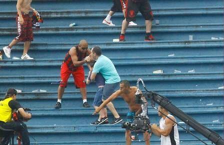 Segurando fortemente o filho Em meio à violência do futebol brasileiro, um pai, uma criança e um consciente. Não se faz copa com violência.