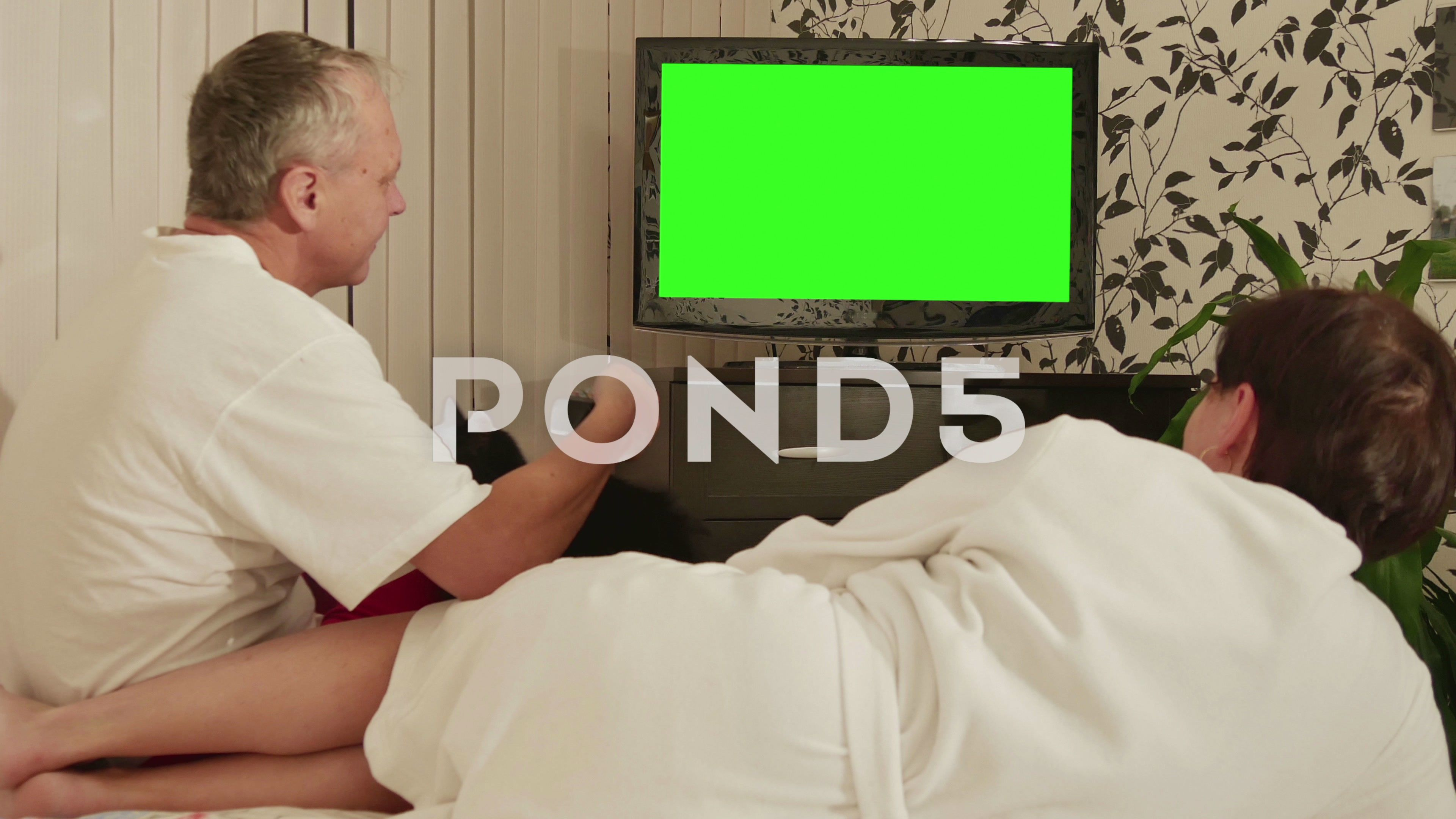 Couple Sitting On The Couch And Watching Tv With Green Screen
