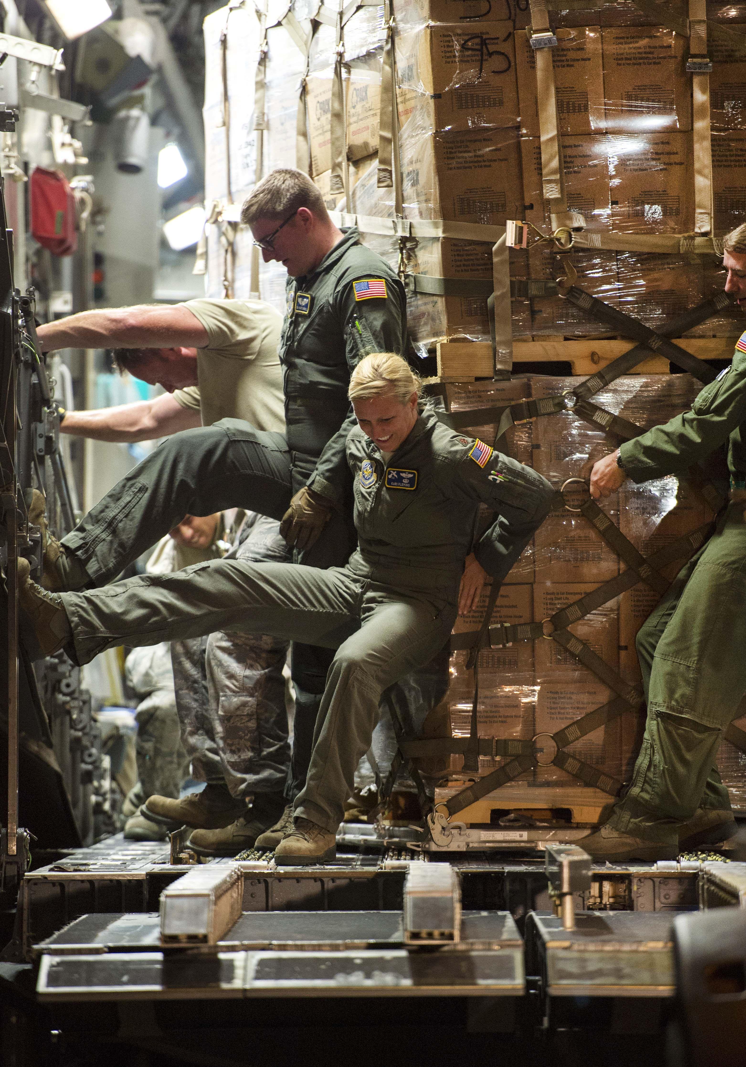 Airmen push a pallet of food off a C17 Globemaster III at