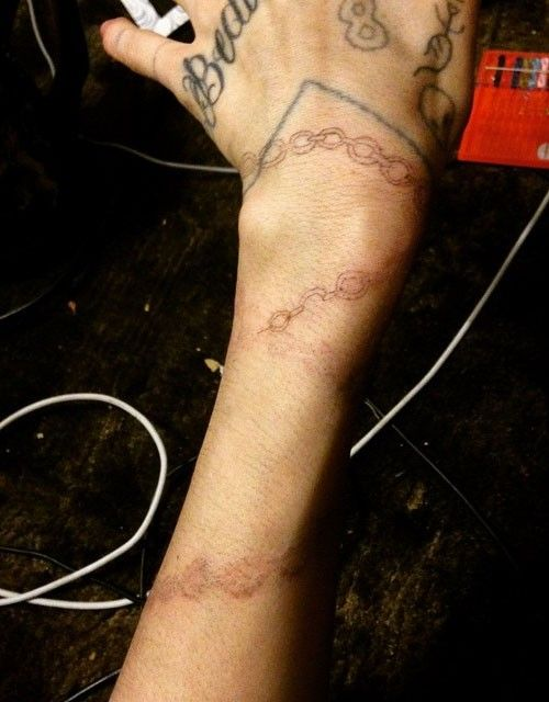Photo of grimes-chain-arm-tattoo