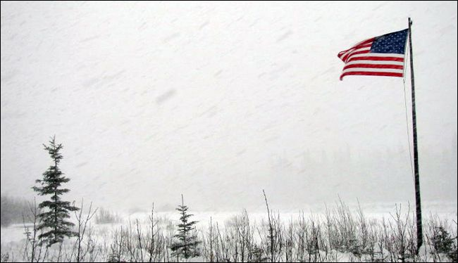 US flag flying during snow storm outside! No snow storm