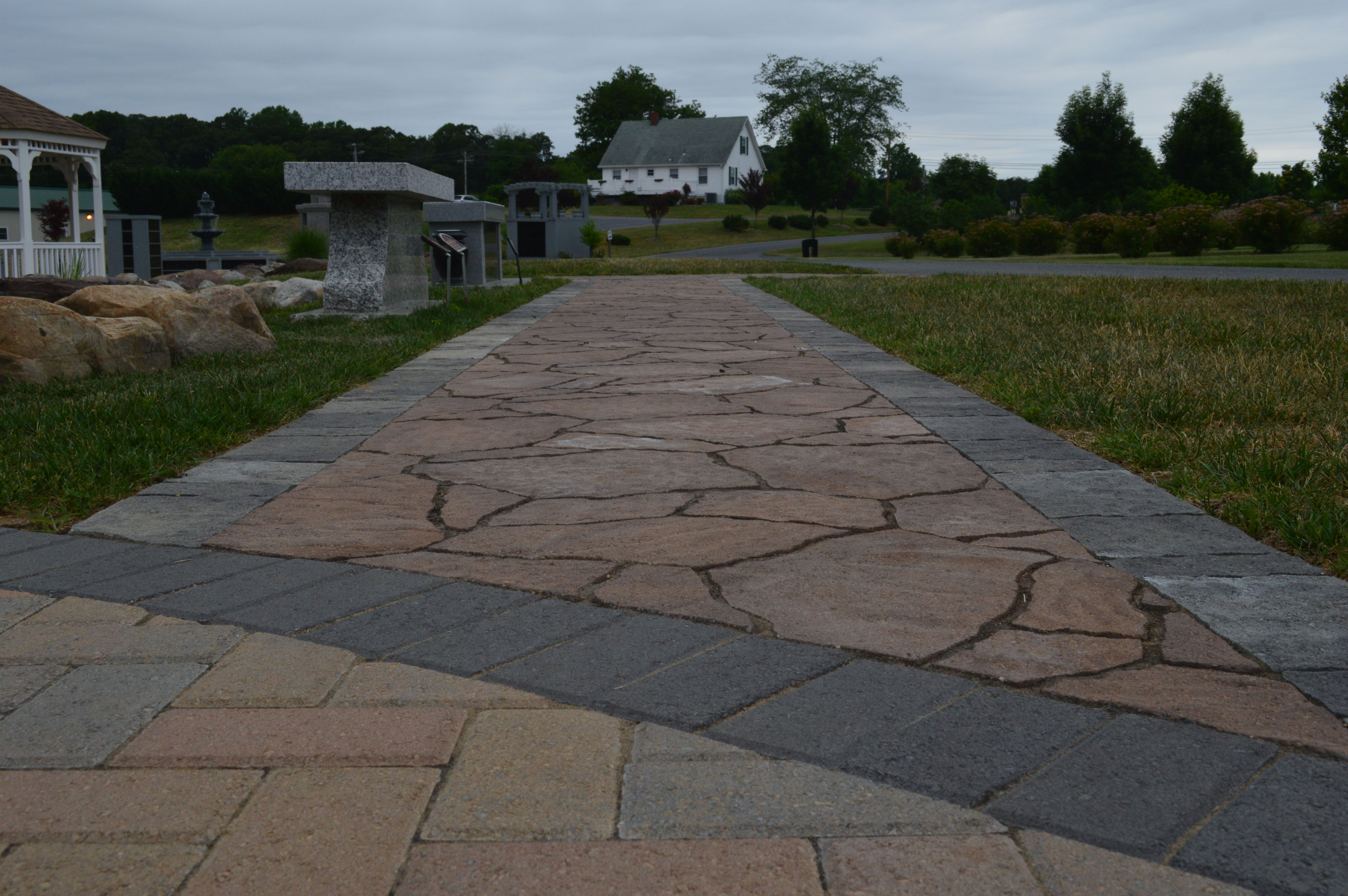The project consists of an Aquascape Inc. ecosystem pond with streams surrounded by Pennsylvania Fieldstone boulders. The walkways are being constructed using Outdoor Living by Belgard pavers. One walkway is Holland Stone pavers and border. the other walkway is Mega Arbel patio slab with a Lafitt border.