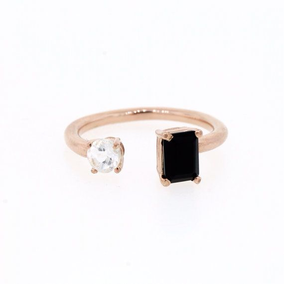 Art Deco inspired, sterling silver ring plated in 18 K rose gold. Prong set emerald cut 6 mm x 4 mm black onyx and 4 mm round white topaz.