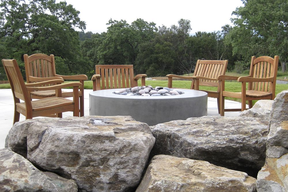 Cleaver Design Associates - Round concrete fire feature surrounded by boulders and wood seating