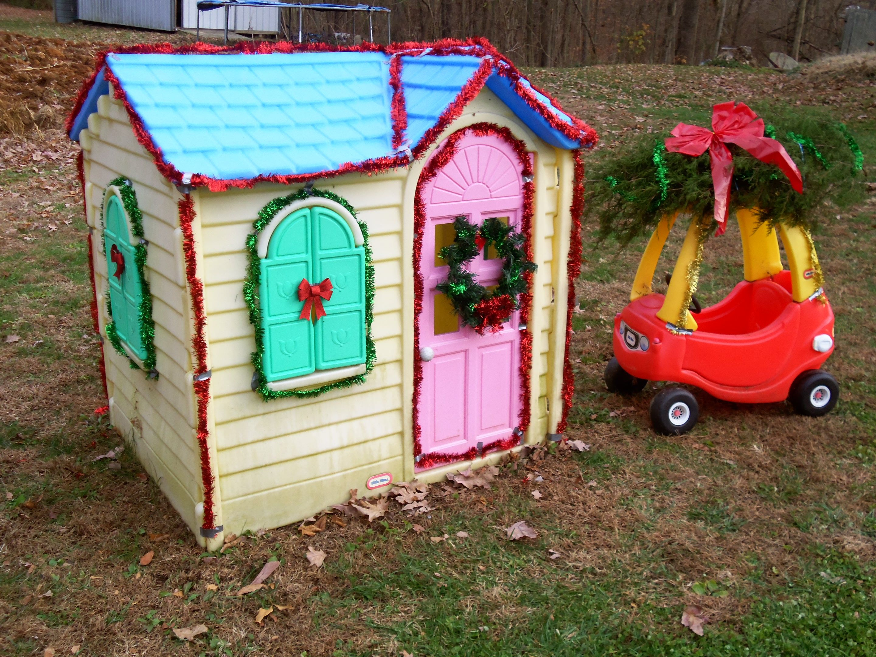 Cosy Little Tikes Home Garden Playhouse. Decorated Little Tikes Playhouse and Cozy Coupe car with Christmas Tree on  top