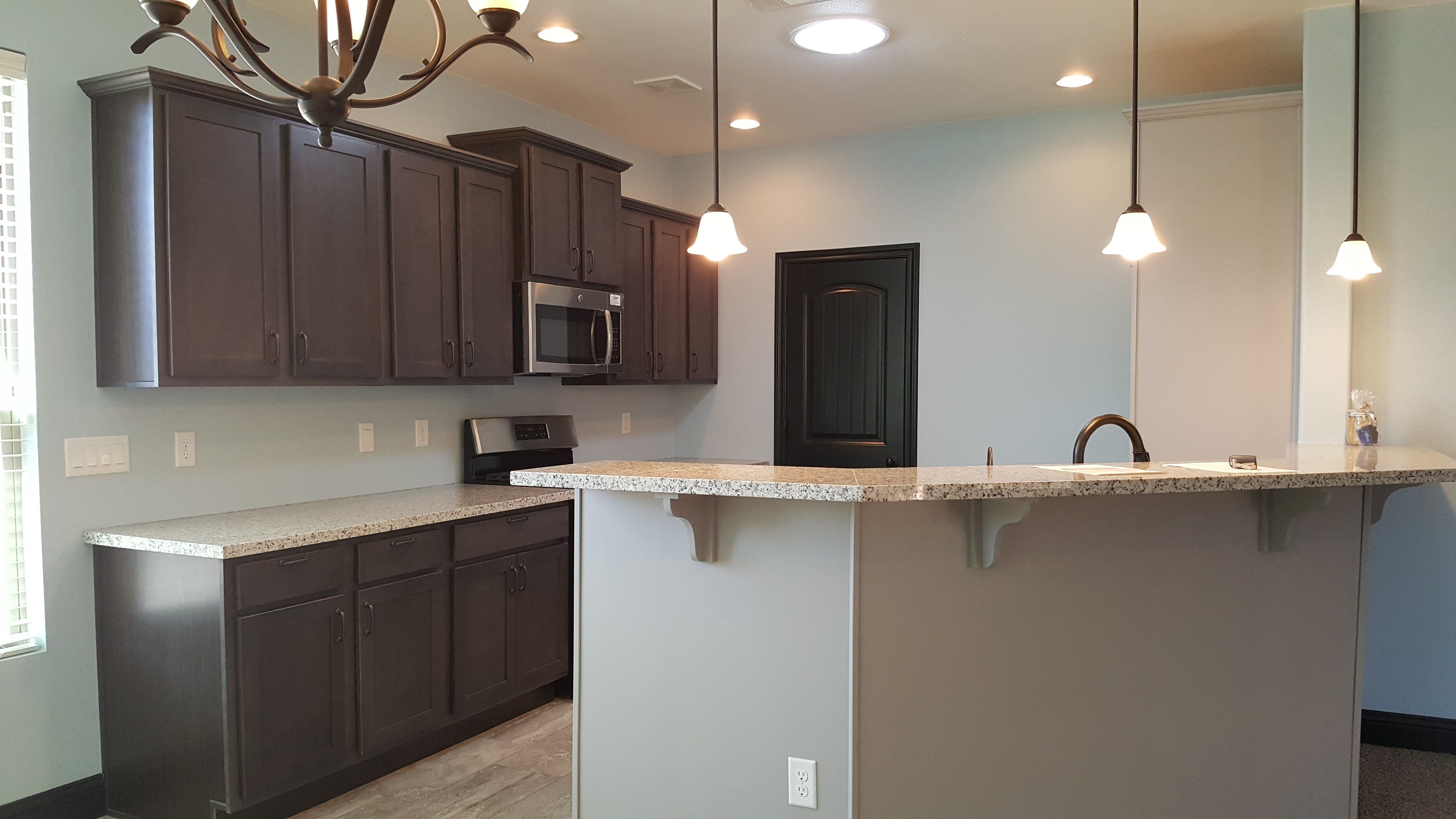 Contrasting Cabinets And A Bright Paint Color Make This Mirella Kitchen Pop Home Bright Paint Colors New Homes