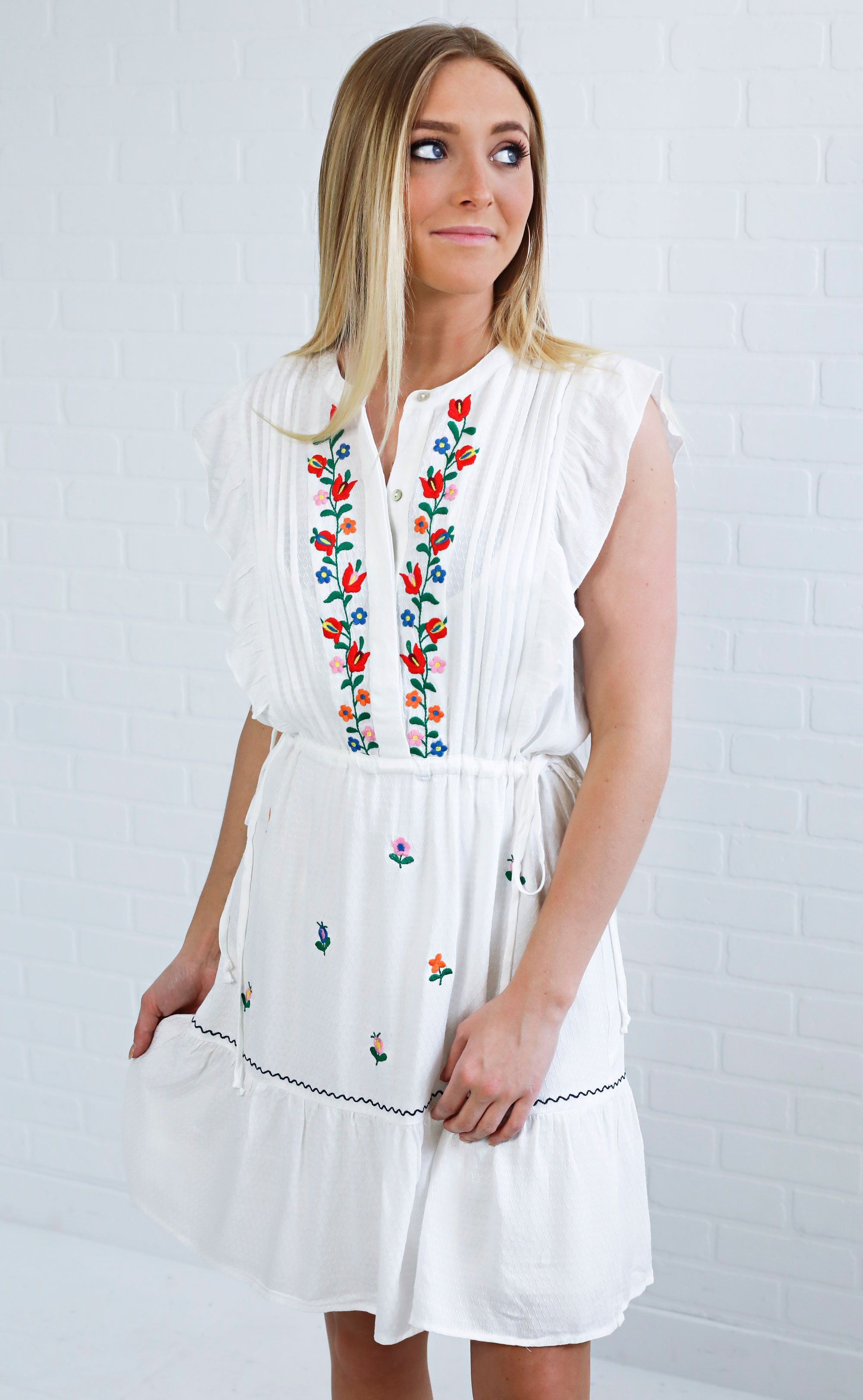 39e9aee42a17 Nothing beats a cute embroidered dress! This one features a button up  placket and has a cinched waist to keep things looking so flattering.