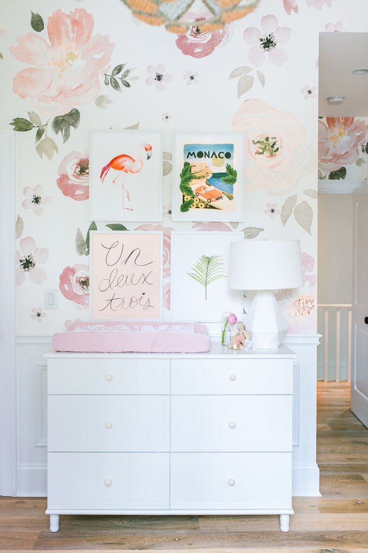 The wall paper and the changing table are so pretty in pink.