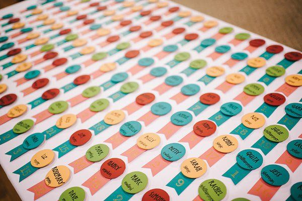 """If you've created seating assignments, you'll need an escort-card display and table cards. Wedding programs, though optional, also serve as keepsakes.Here, colorful escort """"badges."""""""