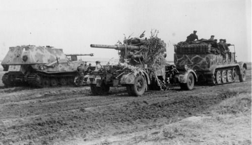 """kruegerwaffen: """" A Sd.Kfz.7 towing an 88mm FlaK 36 or 37 passes a halted Panzerjäger Tiger (P) 'Ferdinand'. Both vehicles have interesting camouflage schemes comprising of a web type patter effect, which has been created by spraying a lighter colour..."""