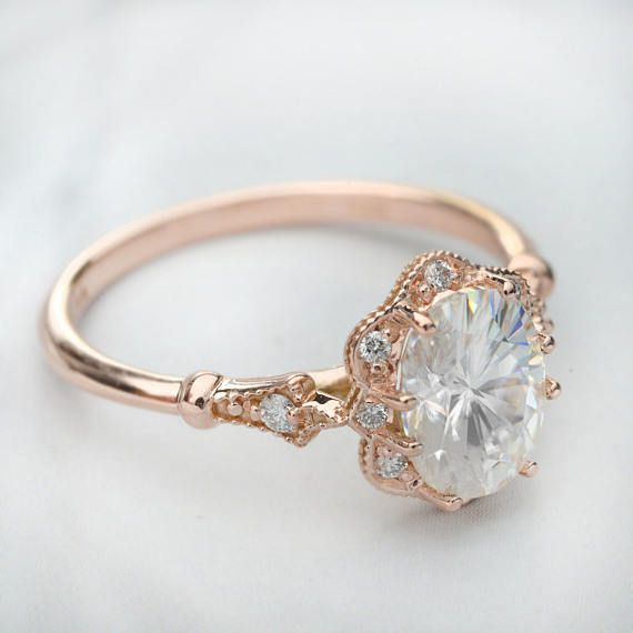 Made to order 14kkt Pink gold engagement ring with 8 diamonds on the halo and two diamonds on the shakn The center stone Charles & Colvard Forever One Moissanite certified 8X6 or 7X5 The setting is made in pink gold with an antique look the halo includes 8 diamonds 1.15mm G-Si quality and the shank 2 diamonds 1.15mm G-SI Total carat weight .09ct Finger sizes from 4 to 10  This ring can also be made with Morganite or Aqua Marina Santa Maria.  All my jewelry is designed and manufactured at...