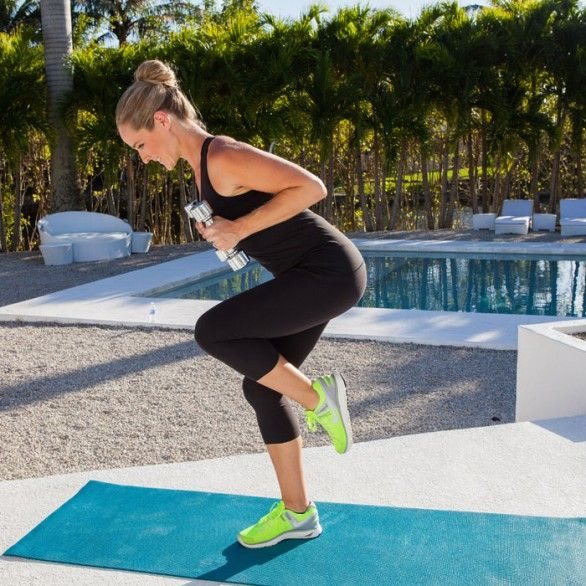 Stand On Right Leg, Holding Dumbbells. Bend Right Knee And