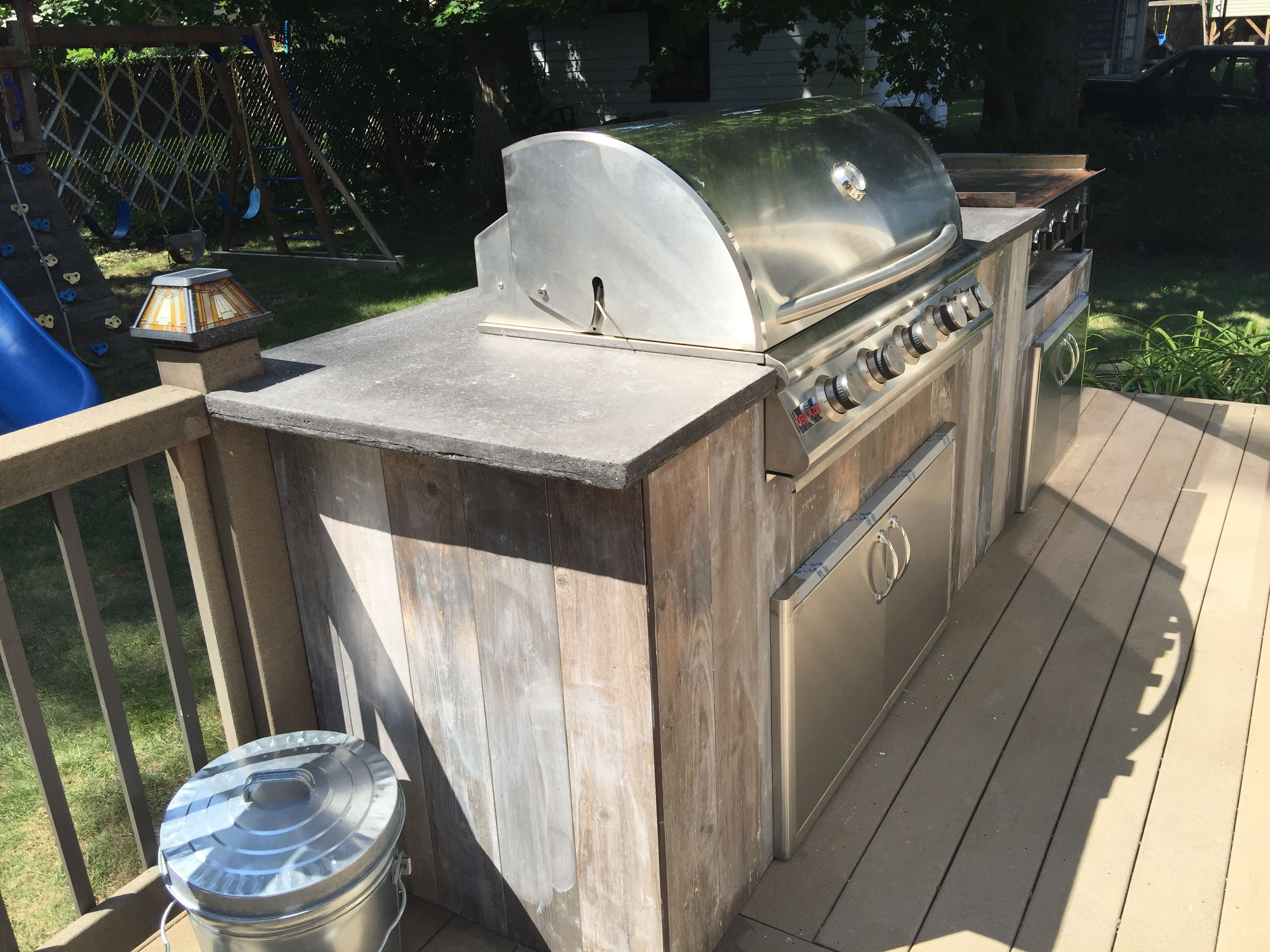 Outdoor Kitchen With Grill And Griddle Station With Concrete Countertop And Reclaimed Wood Tiles Outdoor Kitchen Countertops Outdoor Wood Outdoor Kitchen