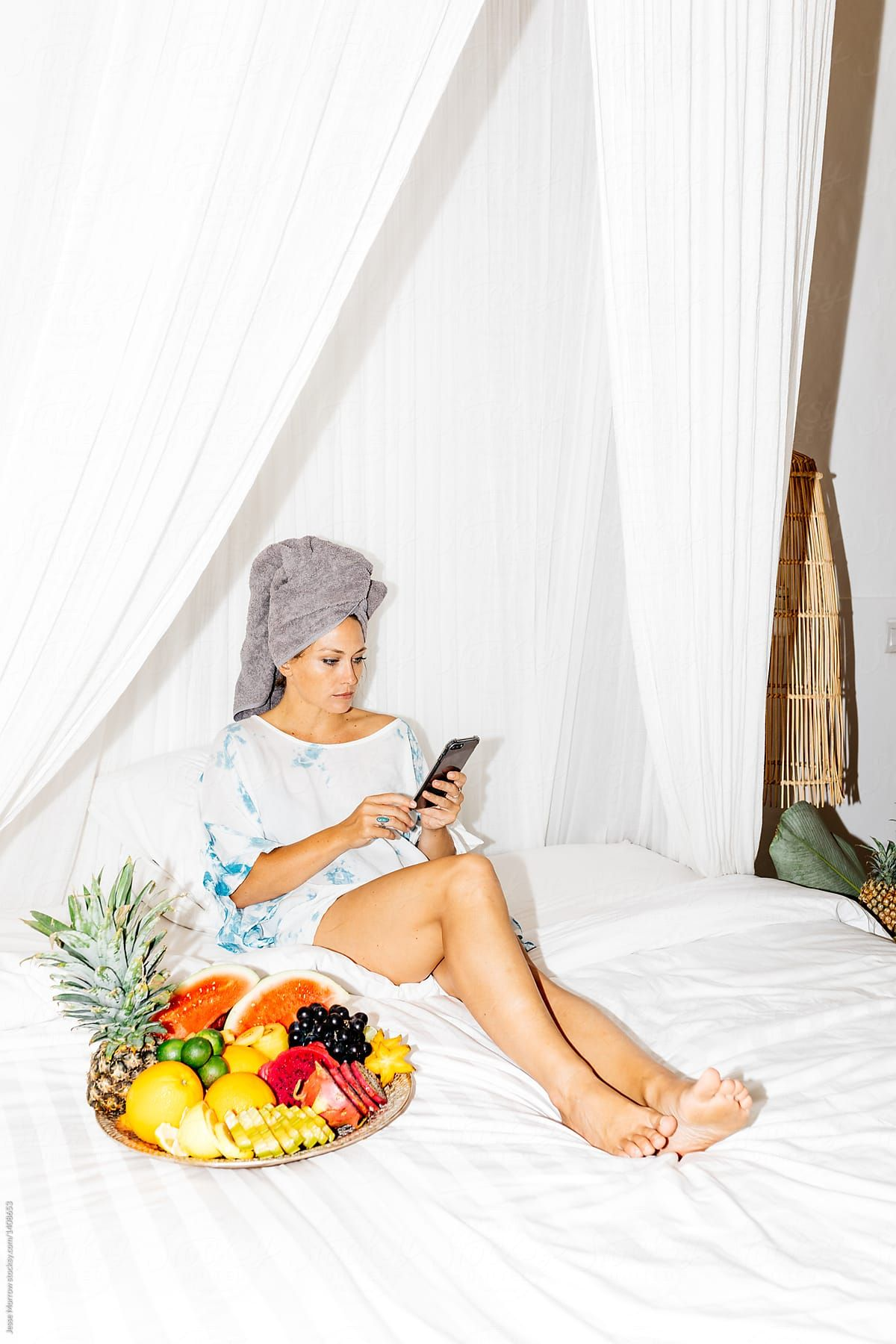 Young Adult Woman Sitting On Bed With Wet Hair And Towel On Head