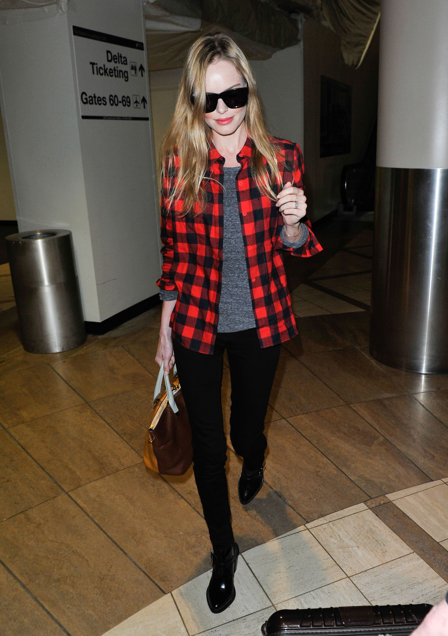 Kate Bosworth at Los Angeles International airport, wearing black pants, low boots and a checked red and black button-up. via @stylelist