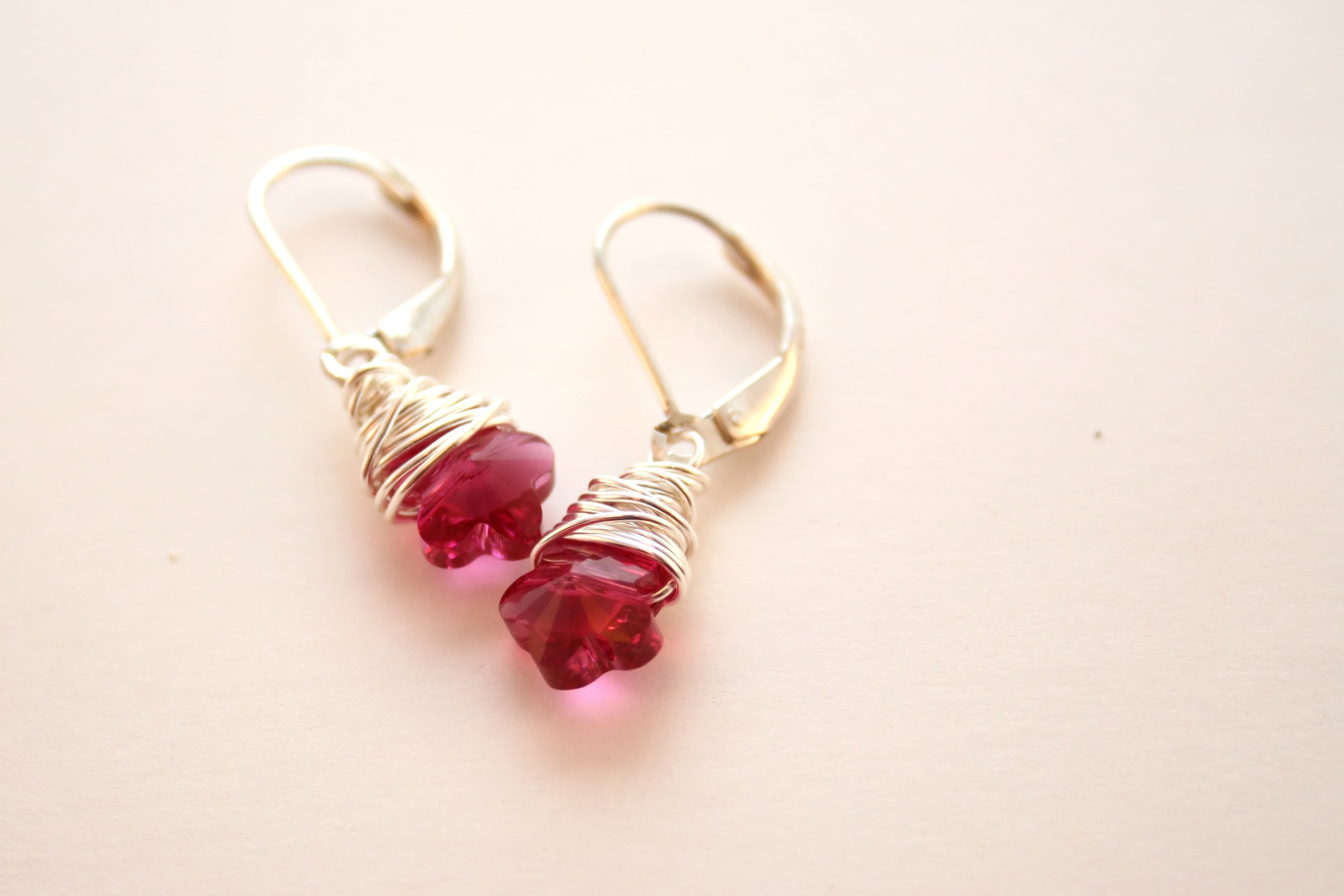 """1002- Sterling Silver Wire Wrapped Fuchsia Swarovski Crystal Flower Earrings $18 Description: Bright and petite sweet flowers ready for your collection!! Wire wrapped with Sterling silver and hung delicately from Sterling silver lever backs. These measure approximately 1"""" from top of the lever backs."""