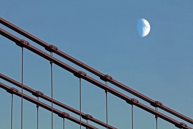 An image of the Suspension bridge on Clyde Street, Glasgow with the moon in the background
