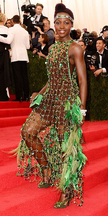 Lupita Nyong'o's Met Gala Gown Gets the Risk-Taker Award | People.com.  Prada net dress featuring a crazy number of embellishments — glass beads, crystals, cascading feathers and chandelier drops. She teamed the look with gem-studded green suede sandals and a coordinating clutch, also Prada. a vintage Cartier necklace worn as a headpiece and oodles of other vintage Cartier jewels.