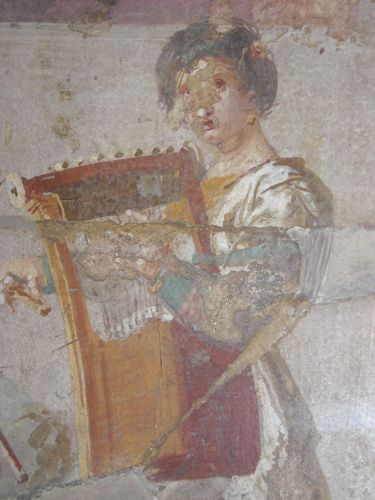 A seated women appears to be reading the musical score being played of a double-flute and cithara - Detail - from Herculaneum - Naples Archaeological Museum