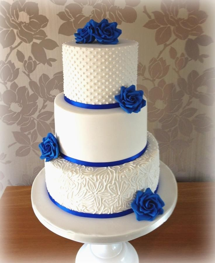 Beautiful Wedding Cake With Royal Blue Flowers And Ribbon