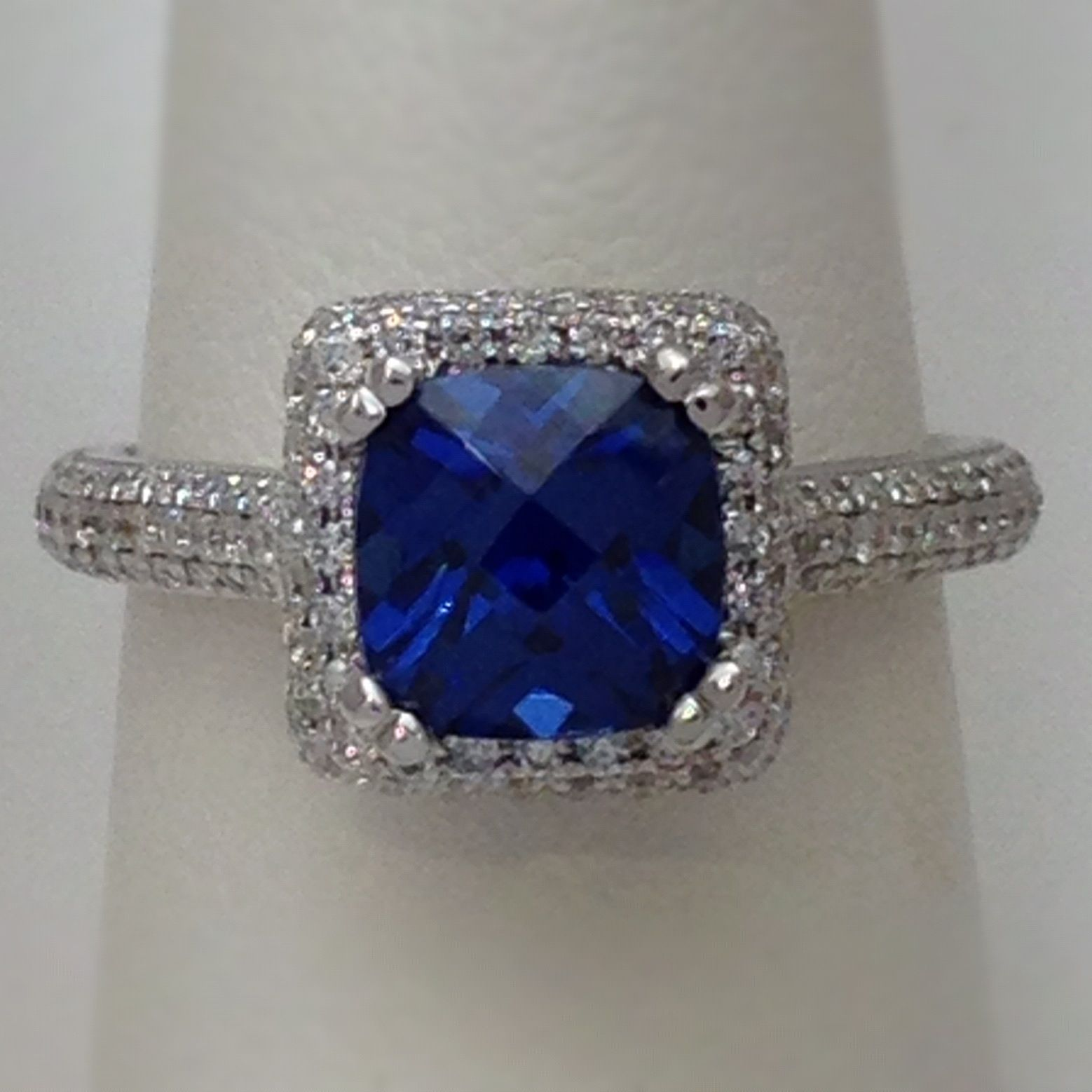 Cushion cut Sapphire and Diamond engagement ring.  The setting is a pave set, halo style ring.