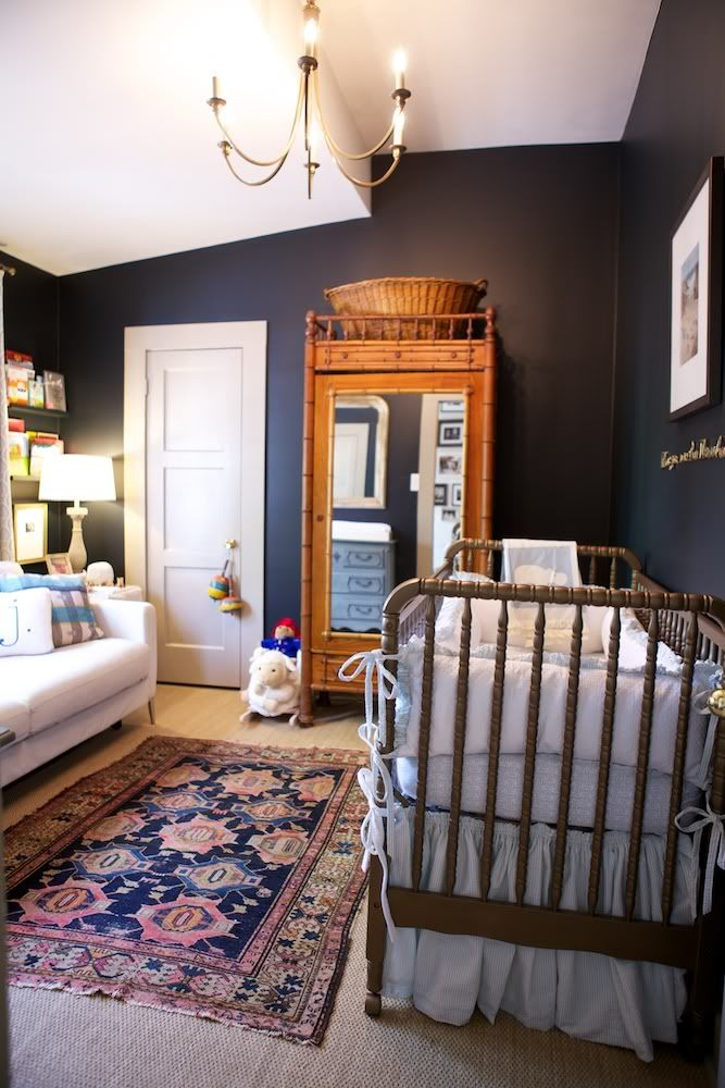 Super dark navy walls lend a richness and a coziness to a bright and sunny nursery from LeSueur Interiors. The rug adds to the magic!