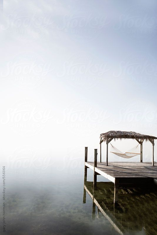 An empty rope hammock under a cabana at end of wooden jetty.